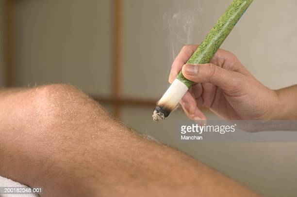 Acupuncturist holding moxa stick above man's leg, close-up