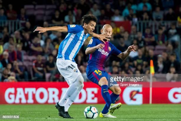 Adalberto Penaranda of Malaga CF competes for the ball with Javier Alejandro Mascherano of FC Barcelona during the La Liga 201718 match between FC...