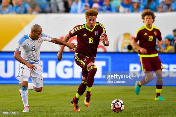 Adalberto Penaranda of Venezuela fights for the ball with Carlos Sanchez of Uruguay during a group C match between Uruguay and Venezuela at Lincoln...