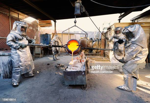 Adalid Orozco Daniel Flores and Jose Sosa in fire suits pour molten bronze metal into molds as Enrique Guerrero looks on during the casting of the...