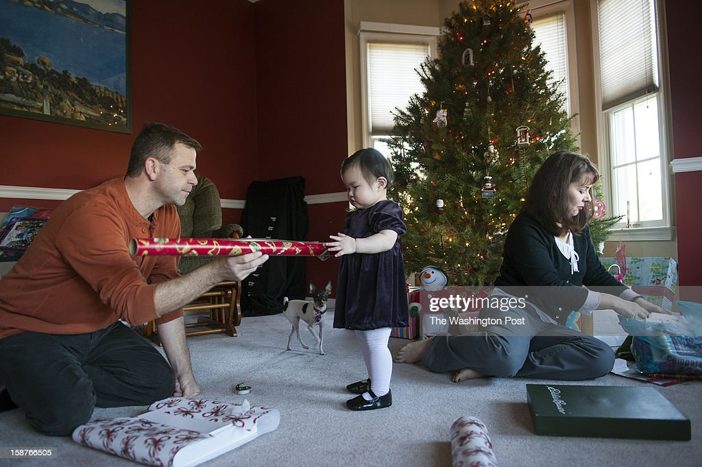 Adam and Carol Raines wrap Christmas presents with help from their newly adopted daughter, Hannah Sunday, December 23, 2012 in Westminster, MD. They waited 2 1/2 years to adopt a child from Korea, and just two weeks ago picked up their 17-month-old daughter. The couple married six years ago, but have been together for 16 years.