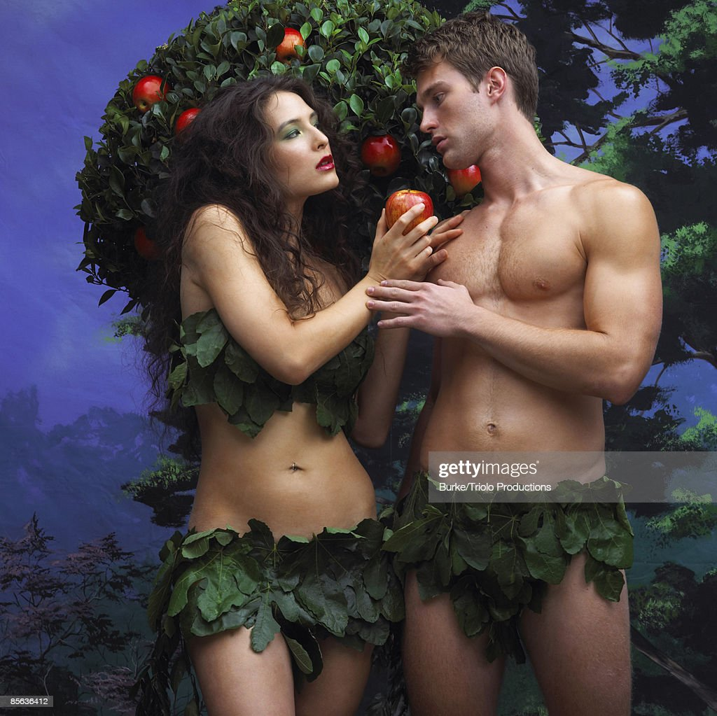 Adam and Eve holding apple near tree : Stock Photo