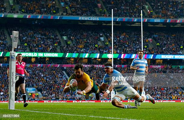 Adam AshleyCooper of Australia dives over to score their second try despite the tackle by Pablo Matera of Argentina during the 2015 Rugby World Cup...