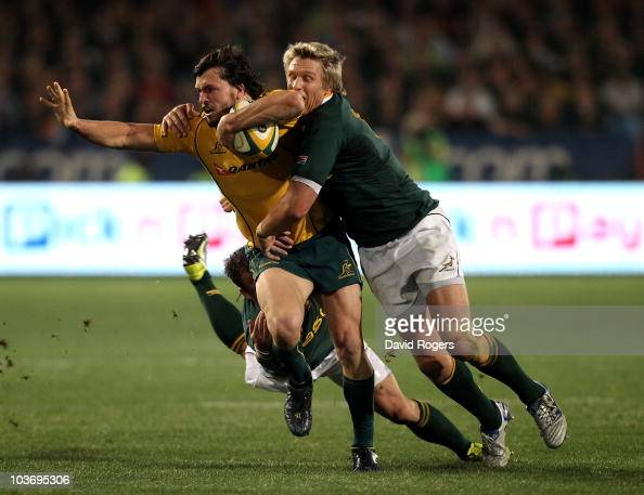 Adam AshleyCooper of the Wallabies is tackled by Francois Hougaard and Jean de Villiers during the 2010 TriNations match between the South African...