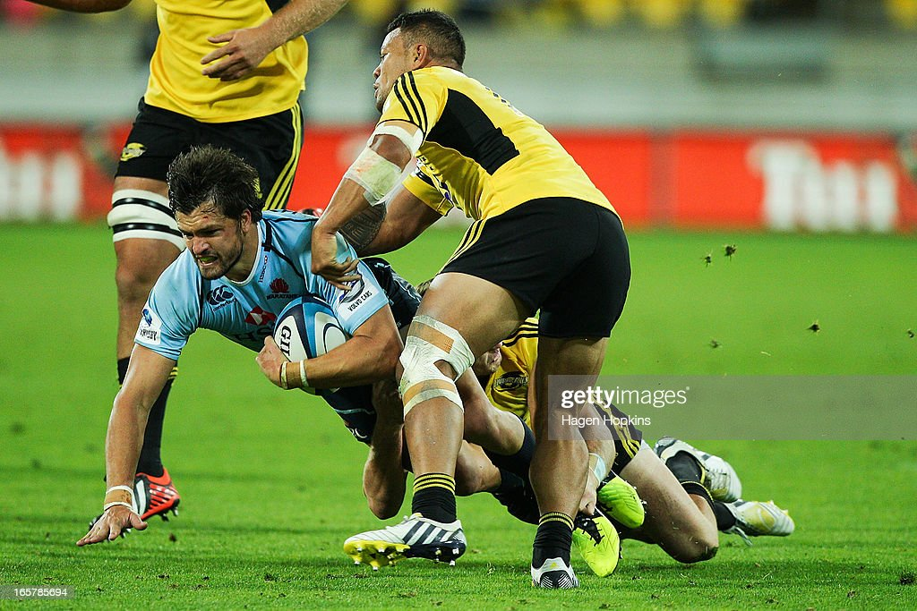 <a gi-track='captionPersonalityLinkClicked' href=/galleries/search?phrase=Adam+Ashley-Cooper&family=editorial&specificpeople=637621 ng-click='$event.stopPropagation()'>Adam Ashley-Cooper</a> of the Waratahs is tackled during the round eight Super Rugby match between the Hurricanes and the Waratahs at Westpac Stadium on April 6, 2013 in Wellington, New Zealand.