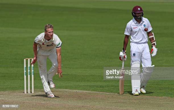 Adam Ball of Kent bowls as Kyle Hope of West Indies backs up during day one of the tour match between Kent and West Indies at The Spitfire Ground on...