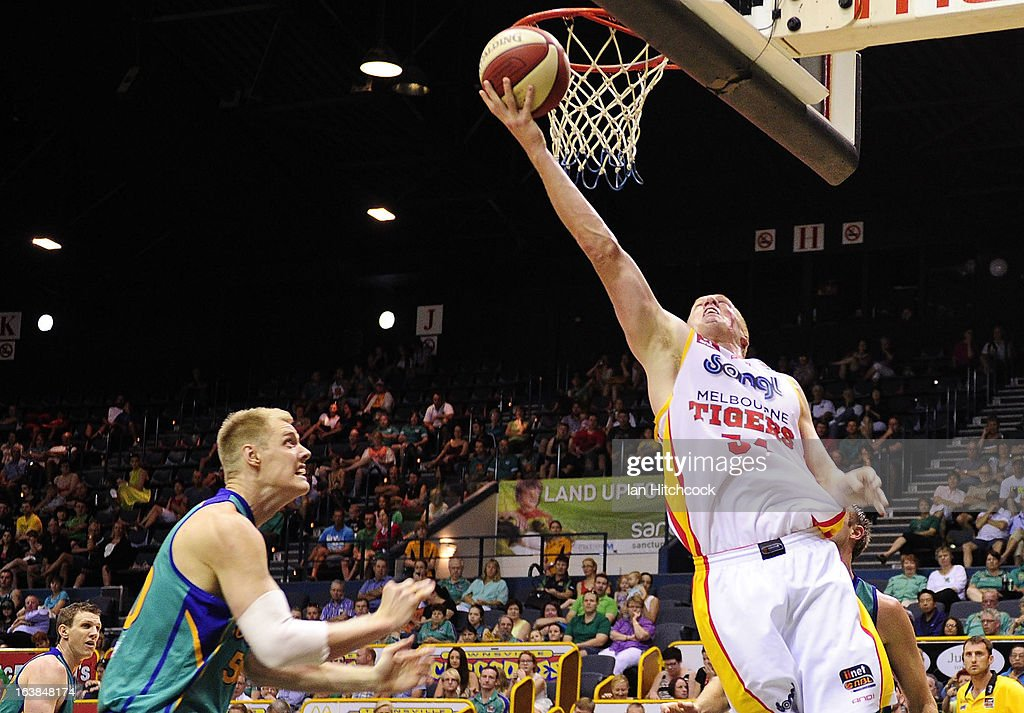 Adam Ballinger of the Tigers atempts a layup ahead of Luke Nevill of the Crocodiles during the round 23 NBL match between the Townsville Crocodiles and the Melbourne Tigers at Townsville Entertainment Centre on March 17, 2013 in Townsville, Australia.