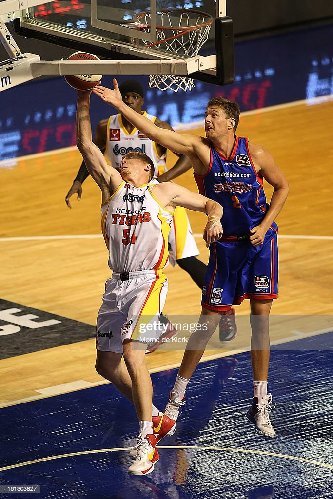 Adam Ballinger of the Tigers blocks a shot by Daniel Johnson of the 36ers during the round 18 NBL match between the Adelaide 36ers and the Melbourne Tigers at Adelaide Arena on February 10, 2013 in Adelaide, Australia.