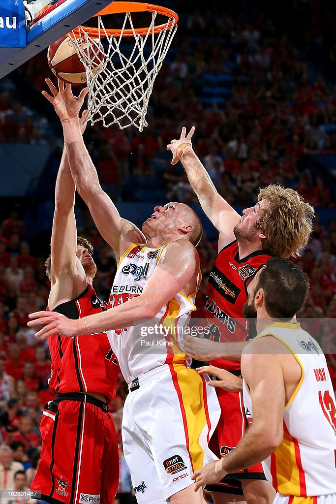 Adam Ballinger of the Tigers contests for a rebound with Cameron Tovey and Jesse Wagstaff of the Wildcats during the round 20 NBL match between the Perth Wildcats and the Melbourne Tigers at Perth Arena on February 21, 2013 in Perth, Australia.