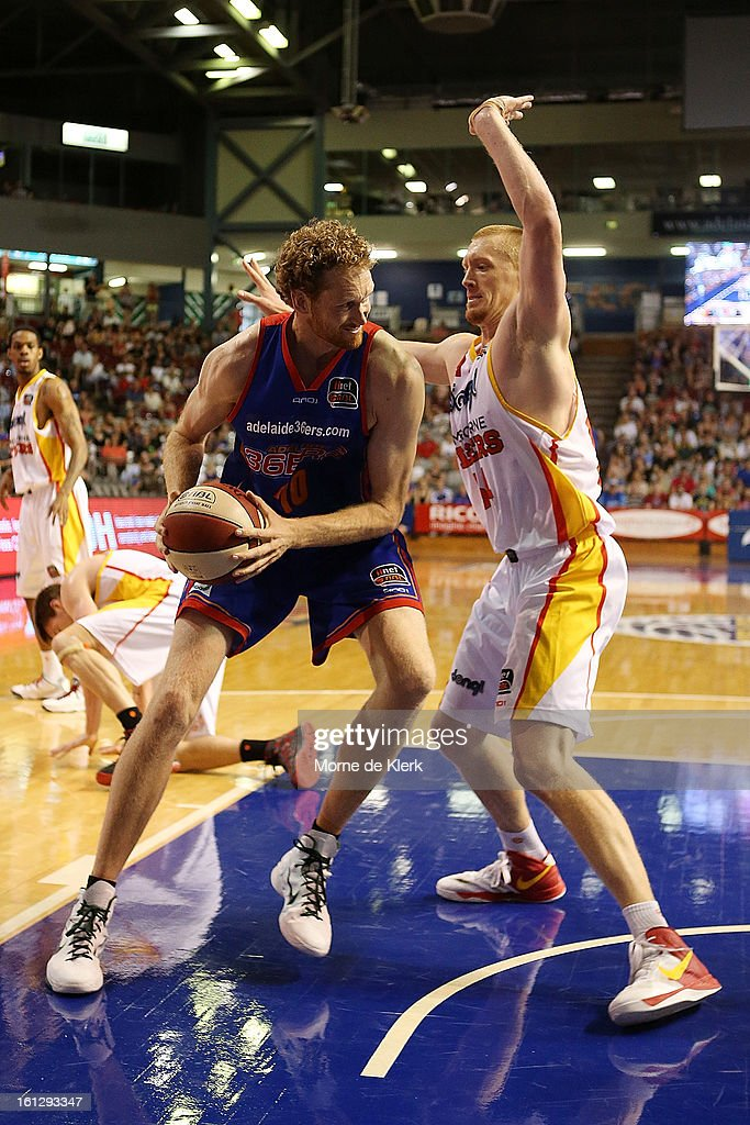 Adam Ballinger of the Tigers defends against Luke Schenscher of the 36ers during the round 18 NBL match between the Adelaide 36ers and the Melbourne Tigers at Adelaide Arena on February 10, 2013 in Adelaide, Australia.