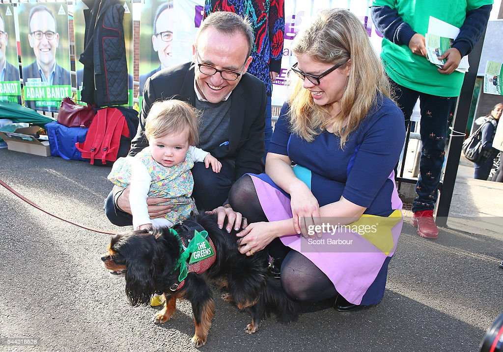 Adam Bandt, Greens Federal Member for Melbourne along with his wife Claudia Bandt and daughter Wren Bandt pat a dog before voting in the national election at a polling station on July 2, 2016 in Melbourne, Australia. Voters head to the polls today to elect the 45th parliament of Australia.