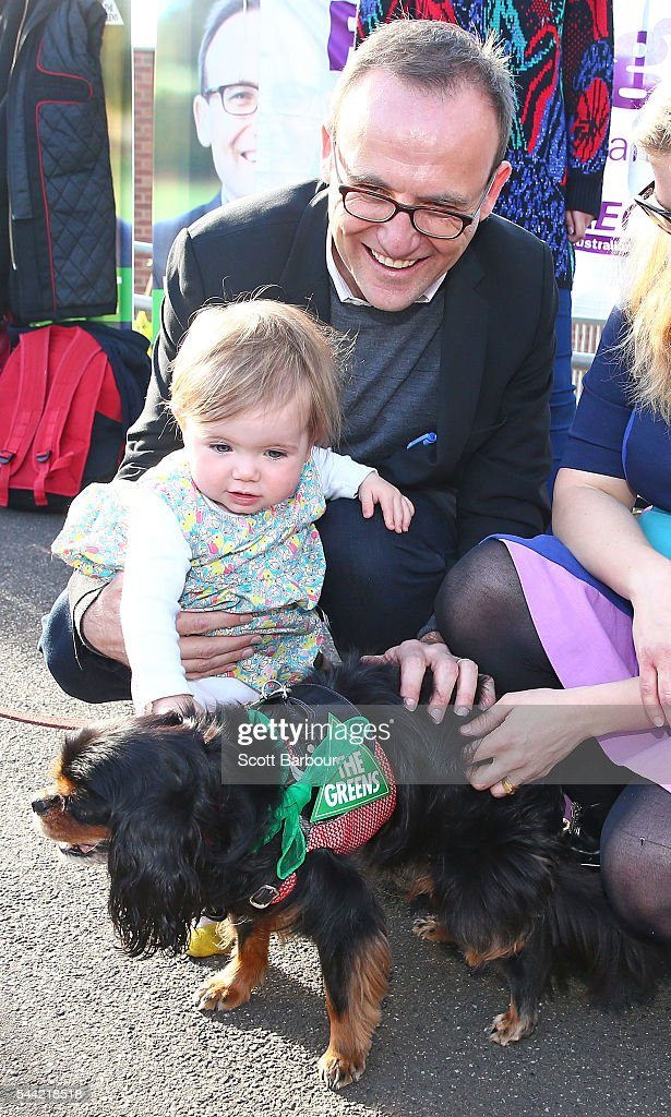 Adam Bandt, Greens Federal Member for Melbourne and his daughter Wren Bandt pat a dog before voting in the national election at a polling station on July 2, 2016 in Melbourne, Australia. Voters head to the polls today to elect the 45th parliament of Australia.