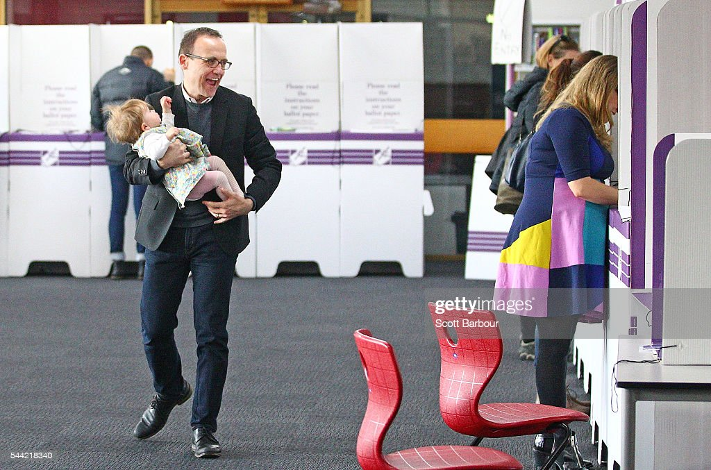 Adam Bandt, Greens Federal Member for Melbourne walks to pick up his daughter Wren after she crawled away as he attempts to vote as his wife Claudia Bandt (R) looks while they vote in the national election at a polling station on July 2, 2016 in Melbourne, Australia. Voters head to the polls today to elect the 45th parliament of Australia.
