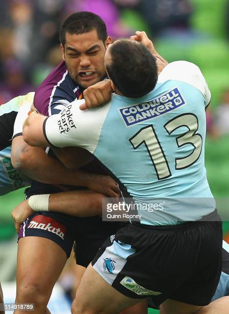 Adam Blair of the Storm fends off a tackle by Paul Gallen of the Sharks during the round 12 NRL match between the Melbourne Storm and the Cronulla...
