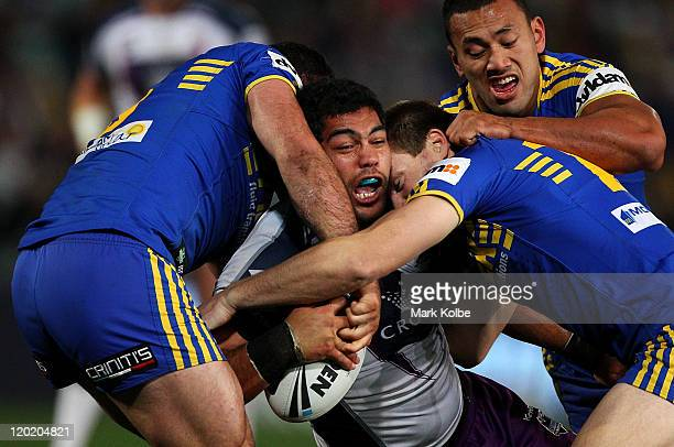 Adam Blair of the Storm is tackled during the round 21 NRL match between the Parramatta Eels and the Melbourne Storm at Parramatta Stadium on August...