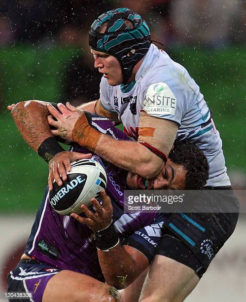 Adam Blair of the Storm is tackled during the round 22 NRL match between the Melbourne Storm and the Penrith Panthers at AAMI Park on August 6 2011...