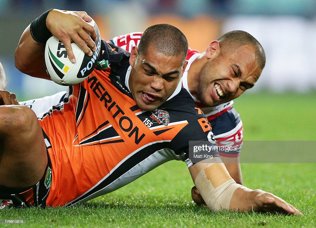 Adam Blair of the Tigers is tackled by James MaloneySam Moathe round 23 NRL match between the Wests Tigers and the Sydney Roosters at Allianz Stadium on August 19, 2013 in Sydney, Australia.
