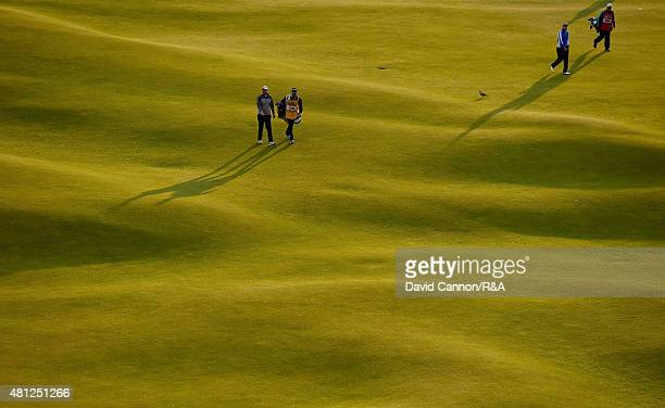 Adam Bland of Australia and his caddie Matthew Butlar along with Daniel Brooks of England and his caddie walk up the 18th hole during the second...