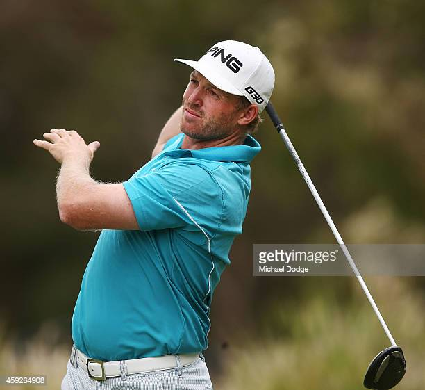 Adam Bland of Australia reacts after his tee shot on the 17th tee during day one of the 2014 Australian Masters at The Metropolitan Golf Course on...