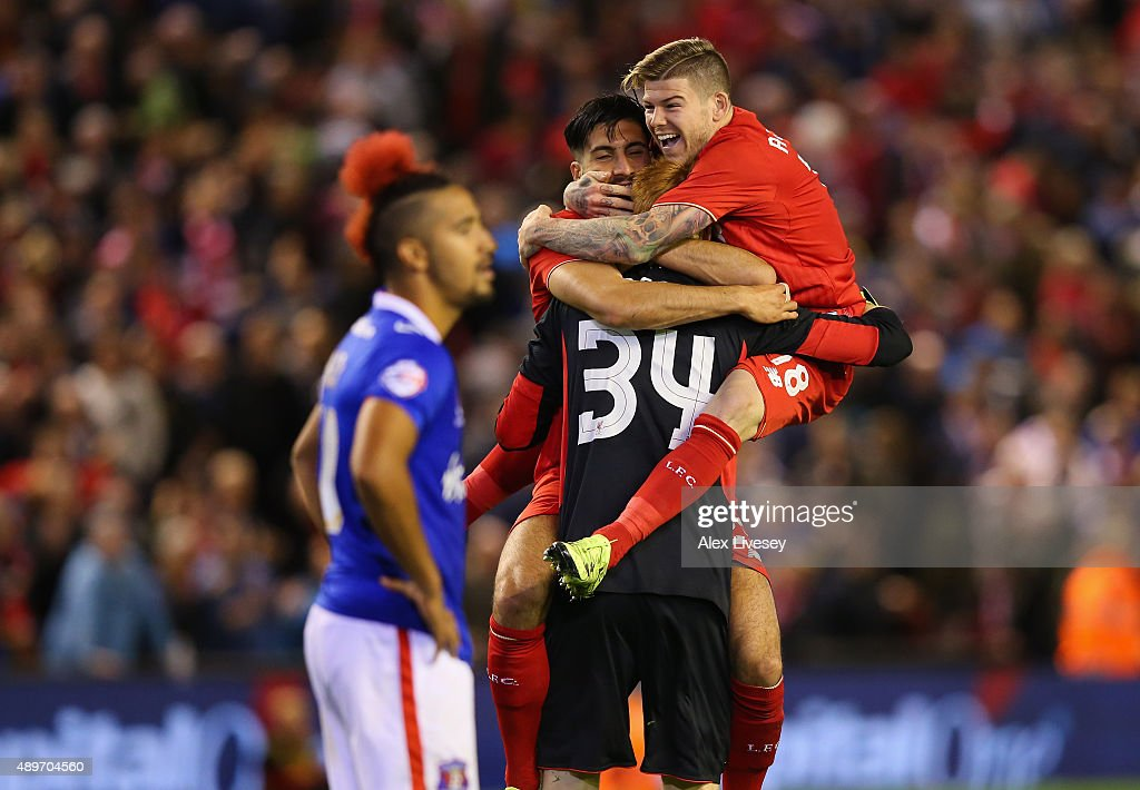 Adam Bogdan of Liverpool celebrates with Alberto Moreno and Emre Can after saving the crucial penalty from Bastien Hery of Carlisle United who looks...