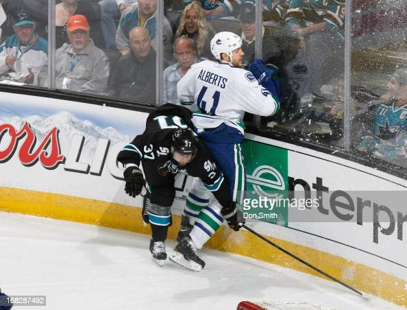 Adam Burish of the San Jose Sharks gets checked by Andrew Alberts of the Vancouver Canucks in Game Four of the Western Conference Quarterfinals...