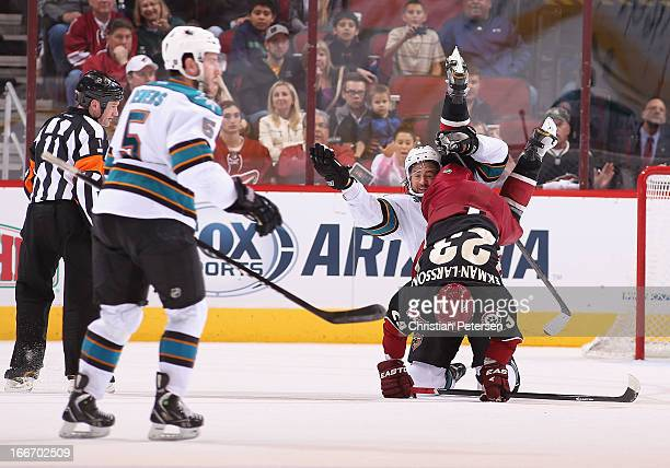 Adam Burish of the San Jose Sharks gets tied up with Oliver EkmanLarsson of the Phoenix Coyotes after a collision during the third period of the NHL...