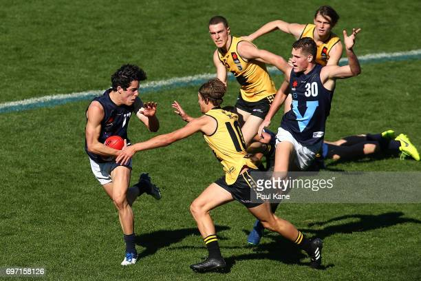 Adam Cerra of Vic Metro fends of a tackle by Connor West of Western Australia during the U18 Championships match between Western Australia and...