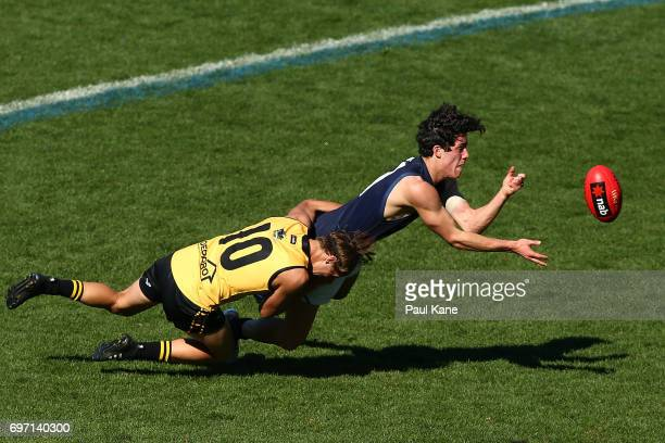 Adam Cerra of Vic Metro gets his handball away while being tackled by Connor West of Western Australia during the U18 Championships match between...