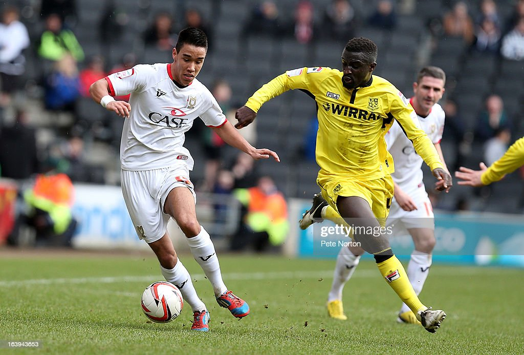 Adam Chicksen of MK Dons controls the ball watched by Zoumana Bakayogo of Tranmere Rovers during the npower League One match between MK Dons and Tranmere Rovers at Stadium MK on March 16, 2013 in Milton Keynes, England.