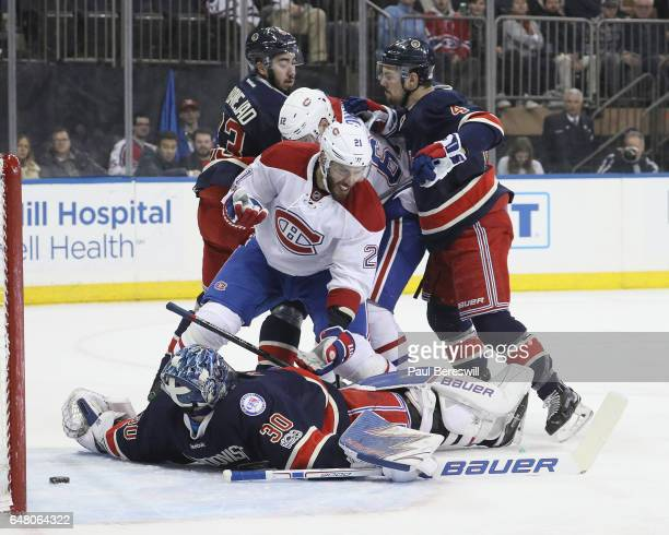 Adam Clendening of the New York Rangers checks Dwight King of the Montreal Canadiens over goalie Henrik Lundqvist of the Rangers as the puck slides...