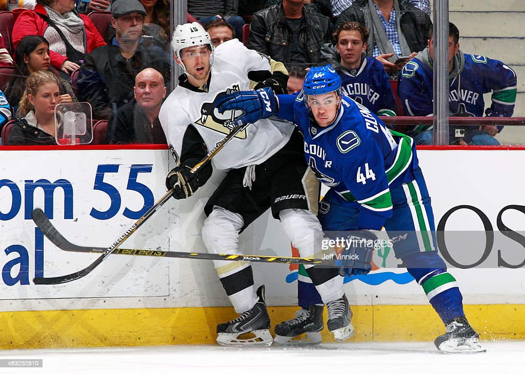 Adam Clendening of the Vancouver Canucks checks Brandon Sutter of the Pittsburgh Penguins during their NHL game at Rogers Arena February 7 2015 in...