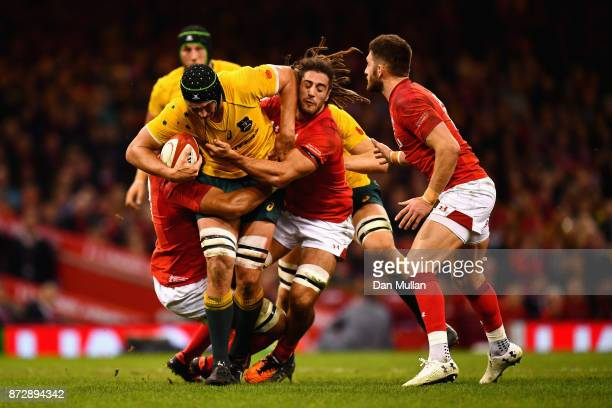 Adam Coleman of Australia is tackled by Josh Navidi of Wales and Taulupe Faletau of Wales during the Under Armour Series match between Wales and...