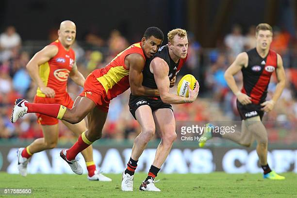 Adam Cooney of the Bombers is tackled by Touk MIller of the Suns during the round one AFL match between the Gold Coast Suns and the Essendon Bombers...