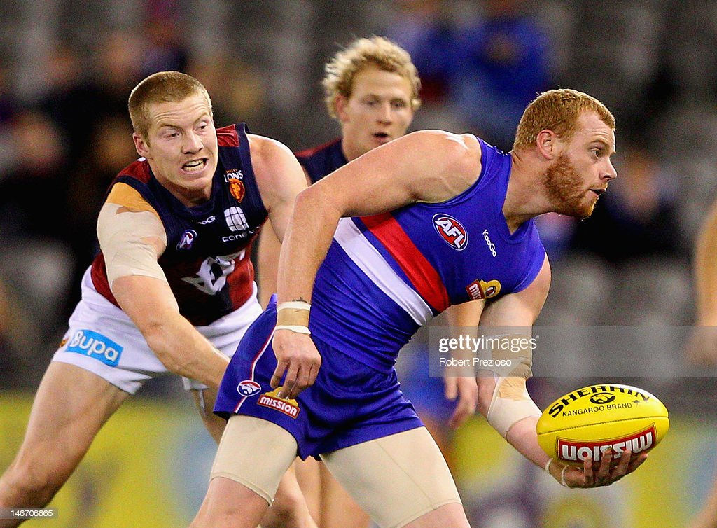 <a gi-track='captionPersonalityLinkClicked' href=/galleries/search?phrase=Adam+Cooney&family=editorial&specificpeople=208786 ng-click='$event.stopPropagation()'>Adam Cooney</a> of the Bulldogs handballs under pressure during the round 13 AFL match between the Western Bulldogs and the Brisbane Lions at Etihad Stadium on June 23, 2012 in Melbourne, Australia.