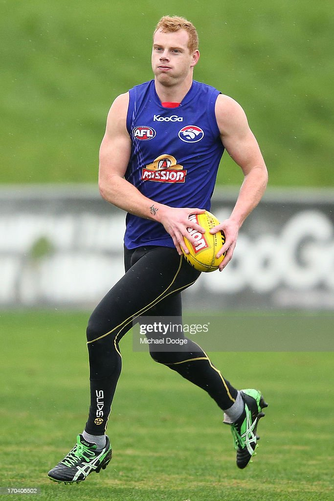 <a gi-track='captionPersonalityLinkClicked' href=/galleries/search?phrase=Adam+Cooney&family=editorial&specificpeople=208786 ng-click='$event.stopPropagation()'>Adam Cooney</a> runs with the ball during a Western Bulldogs AFL training session at Whitten Oval on June 13, 2013 in Melbourne, Australia.