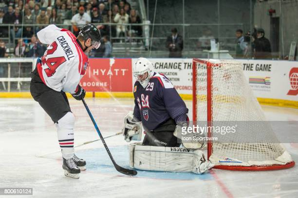 Adam Cracknell of Team Canada attempts to control the puck past Joseph Fallon of Team USA during the Melbourne Game of the Ice Hockey Classic on June...