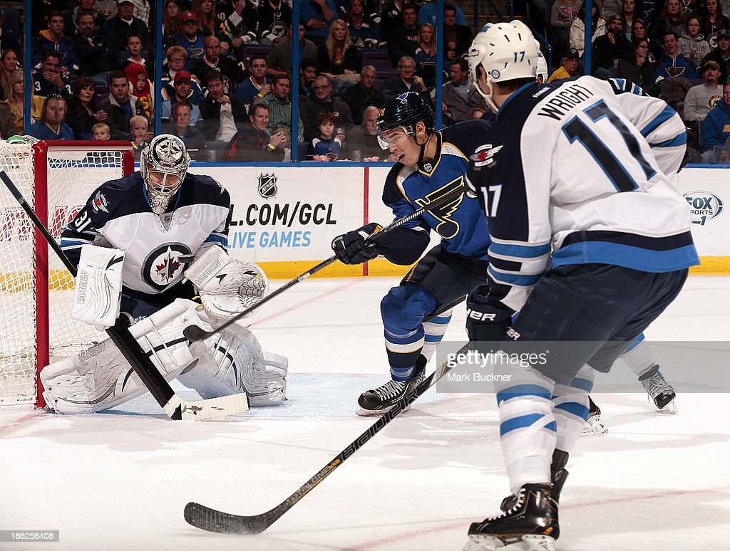 <a gi-track='captionPersonalityLinkClicked' href=/galleries/search?phrase=Adam+Cracknell&family=editorial&specificpeople=2221797 ng-click='$event.stopPropagation()'>Adam Cracknell</a> #79 of the St. Louis Blues tries to poke the puck past Ondrej Pavelec #31 of the Winnipeg Jets on October 29, 2013 at Scottrade Center in St. Louis, Missouri.