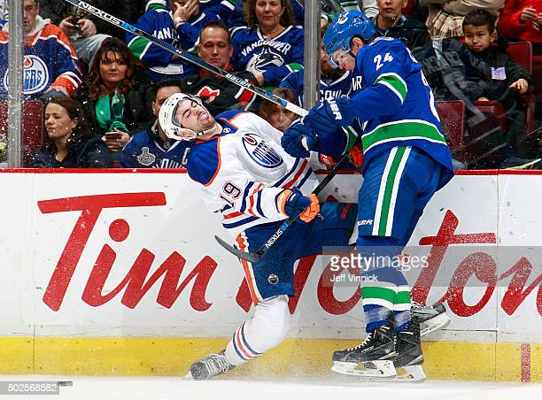 Adam Cracknell of the Vancouver Canucks collides with Justin Schultz of the Edmonton Oilers during their NHL game at Rogers Arena December 26 2015 in...
