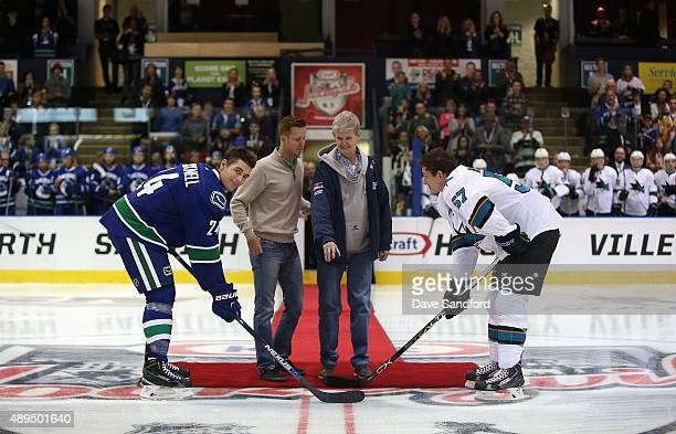 Adam Cracknell of the Vancouver Canucks takes part in a ceremonial faceoff with Tommy Wingels of the San Jose Sharks as Larry Orr drops the puck...