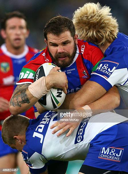 Adam Cuthbertson of the Knights is tackled by James Graham and Trent Hodkinson during the round 8 NRL match between the CanteburyBankstown Bulldogs...