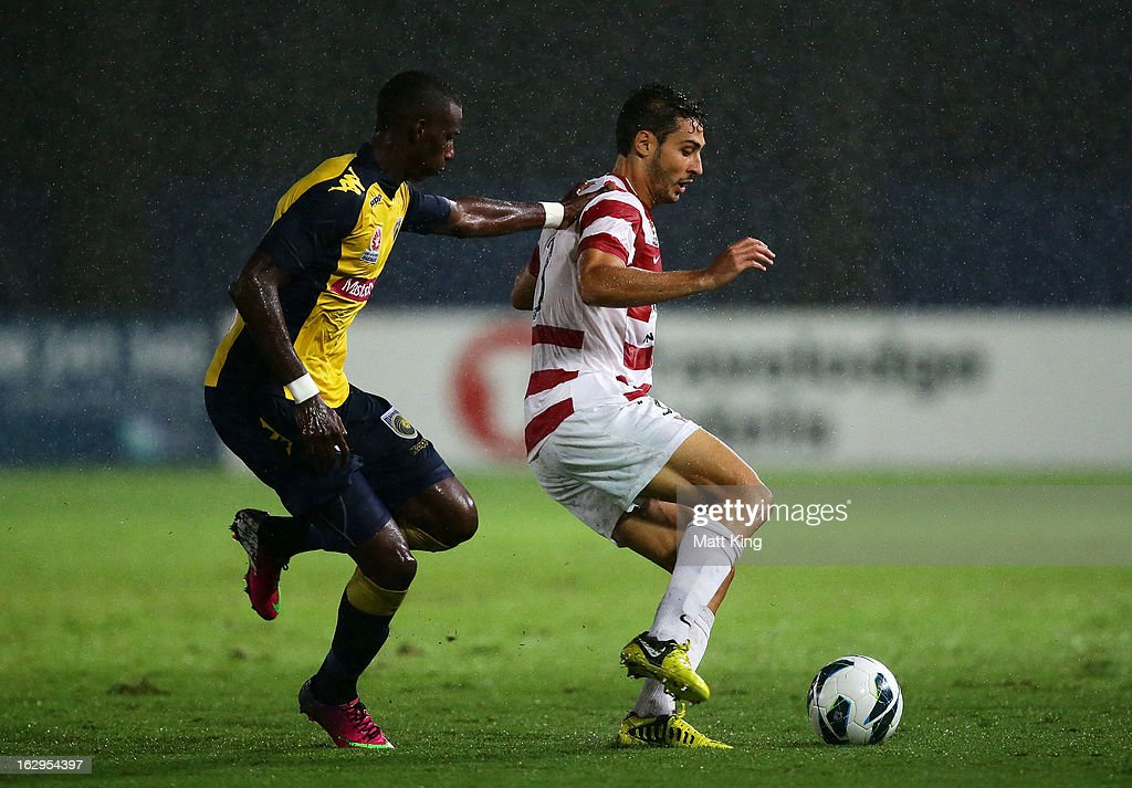 Adam D'Apuzzo of the Wanderers is challenged by Bernie Ibini of the Mariners during the round 23 A-League match between the Central Coast Mariners and the Western Sydney Wanderers at Bluetongue Stadium on March 2, 2013 in Gosford, Australia.