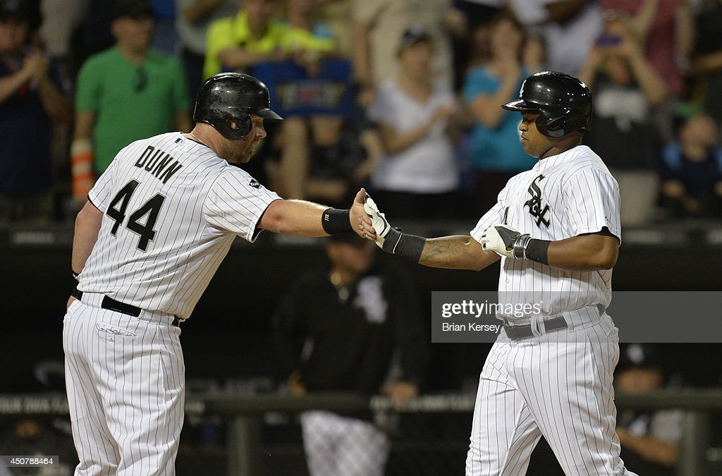 <a gi-track='captionPersonalityLinkClicked' href=/galleries/search?phrase=Adam+Dunn&family=editorial&specificpeople=213505 ng-click='$event.stopPropagation()'>Adam Dunn</a> #44 of the Chicago White Sox (L) congratulates teammate <a gi-track='captionPersonalityLinkClicked' href=/galleries/search?phrase=Dayan+Viciedo&family=editorial&specificpeople=5720224 ng-click='$event.stopPropagation()'>Dayan Viciedo</a> #24 at home plate after Viciedo hit a two-run home run scoring Dunn during the fifth inning against the San Francisco Giants at U.S. Cellular Field on June 17, 2014 in Chicago, Illinois.
