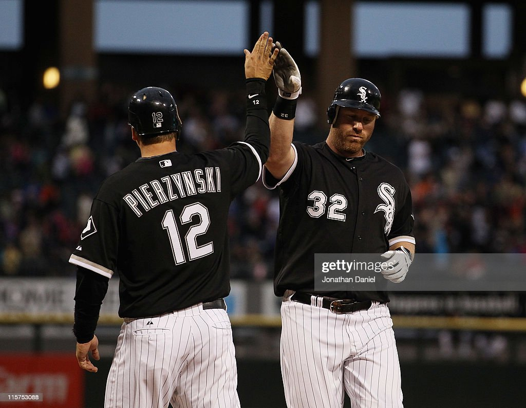 <a gi-track='captionPersonalityLinkClicked' href=/galleries/search?phrase=Adam+Dunn&family=editorial&specificpeople=213505 ng-click='$event.stopPropagation()'>Adam Dunn</a> #32 of the Chicago White Sox is congratulated by teammate <a gi-track='captionPersonalityLinkClicked' href=/galleries/search?phrase=A.J.+Pierzynski&family=editorial&specificpeople=204486 ng-click='$event.stopPropagation()'>A.J. Pierzynski</a> #12 after hitting a two-run home run in the 3rd inning against the Oakland Athletics at U.S. Cellular Field on June 9, 2011 in Chicago, Illinois.