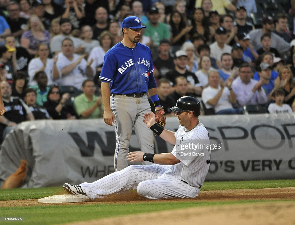 Adam Dunn #32 of the Chicago White Sox is safe at third base as Mark DeRosa #16 of the Toronto Blue Jays looks on during the fourth inning on June 11, 2013 at U.S. Cellular Field in Chicago, Illinois.