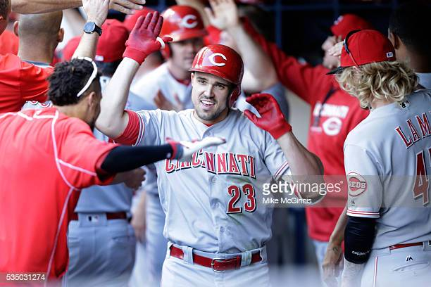 Adam Duvall of the Cincinnati Reds celebrates in the dugout after hitting a three run homer in the seventh inning against the Milwaukee Brewers at...