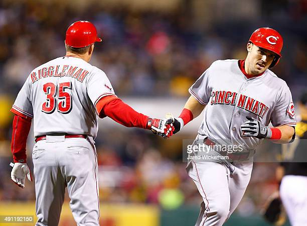 Adam Duvall of the Cincinnati Reds is congratulated by third base coach Jim Riggleman after hitting a solo home run in the 7th inning against the...