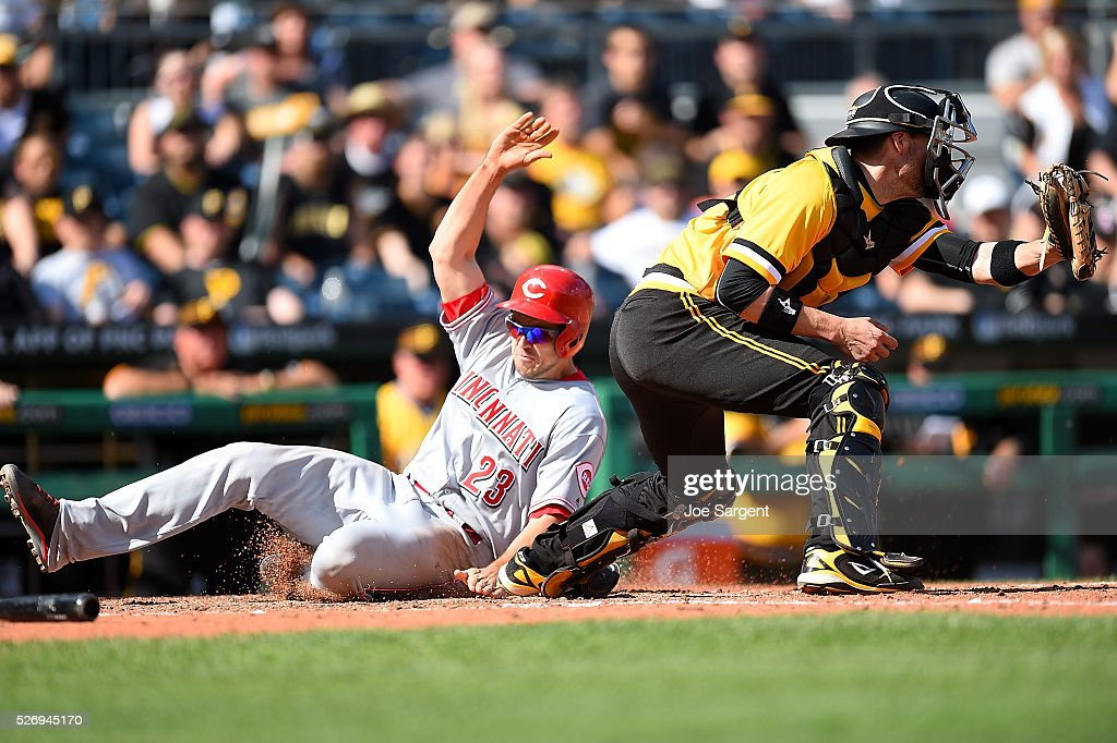 Adam Duvall #23 of the Cincinnati Reds scores in front of Chris Stewart #19 of the Pittsburgh Pirates during the ninth inning on May 1, 2016 at PNC Park in Pittsburgh, Pennsylvania.