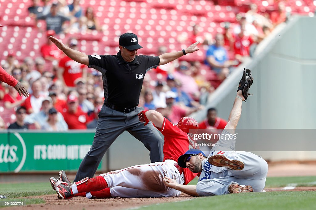 Adam Duvall of the Cincinnati Reds slides into third base ahead of the tag by Rob Segedin of the Los Angeles Dodgers with an RBI triple in the first...