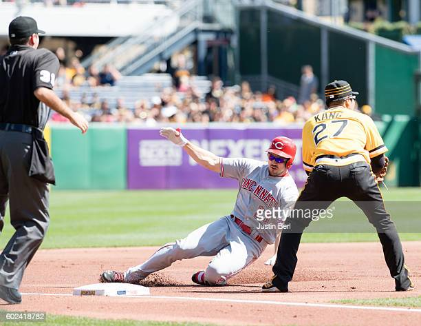 Adam Duvall of the Cincinnati Reds slides safely past Jung Ho Kang of the Pittsburgh Pirates for a triple in the second inning during the game at PNC...