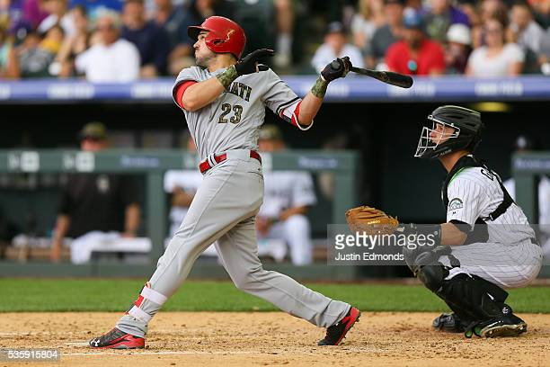 Adam Duvall of the Cincinnati Reds watches his two run home run during the fourth inning as catcher Dustin Garneau of the Colorado Rockies looks on...